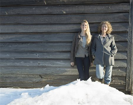 A mother and daughter standing leaning against the wooden wall of a barn on a farm. Snow piled up at their feet. Stock Photo - Premium Royalty-Free, Code: 6118-07440763