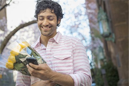 rose patterns - City life. A young man in the park in spring, using a mobile phone.  Holding a bunch of yellow roses. Stock Photo - Premium Royalty-Free, Code: 6118-07440875