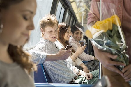 Urban Lifestyle. A group of people, men and women on a city bus, in New York city. Two people checking their smart phones. Stock Photo - Premium Royalty-Free, Code: 6118-07440881