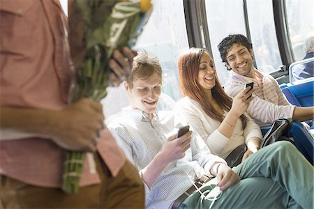 Urban Lifestyle. A group of people, men and women on a city bus, in New York city. Two people checking their phones. One man standing holding a bunch of flowers. Stock Photo - Premium Royalty-Free, Code: 6118-07440882