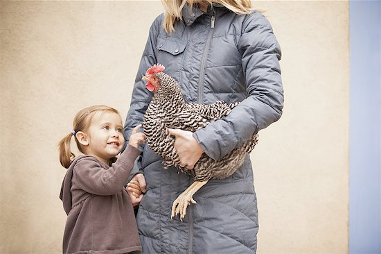 A woman in a grey coat holding a black and white chicken with a red coxcomb under one arm. A young girl beside her holding her other hand Stock Photo - Premium Royalty-Free, Image code: 6118-07440888