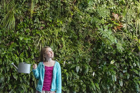 elementary age - A young girl standing in front of a wall covered with ferns and climbing plants. Stock Photo - Premium Royalty-Free, Code: 6118-07441051