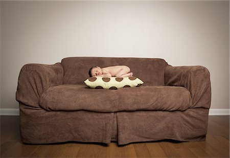 A naked newborn baby lying on his front, sleeping on a pillow on a brown couch. Stock Photo - Premium Royalty-Free, Code: 6118-07441013