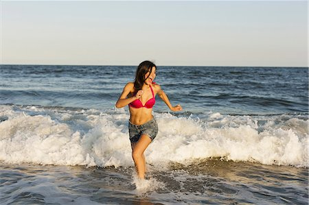 A beautiful young women at the water's edge on the beach in Atlantic City. Stock Photo - Premium Royalty-Free, Code: 6118-07521789