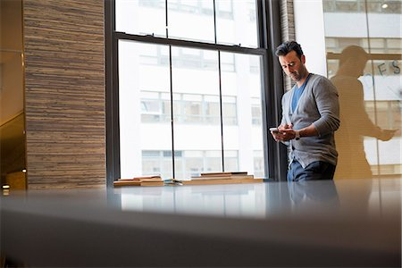 Office life. A man standing by a window in an office checking his smart phone. Stock Photo - Premium Royalty-Free, Code: 6118-07769479