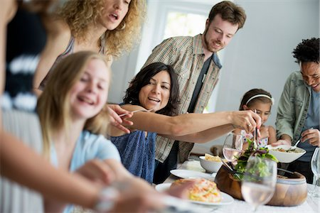 A family gathering for a meal. Adults and children around a table. Stock Photo - Premium Royalty-Free, Code: 6118-07769544