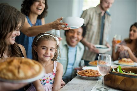 A family gathering for a meal. Adults and children around a table. Stock Photo - Premium Royalty-Free, Code: 6118-07769548