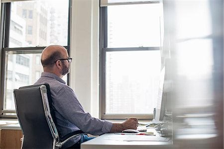 Office life. A man sitting at a desk using a computer, looking intently at the screen. Stock Photo - Premium Royalty-Free, Code: 6118-07769529