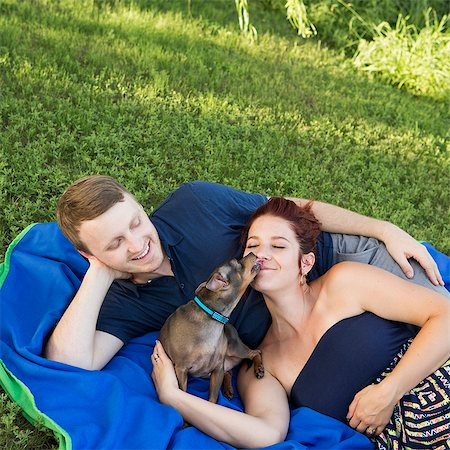 A couple sitting on a picnic rug. A small dog licking the face of a woman. Stock Photo - Premium Royalty-Free, Code: 6118-07781666