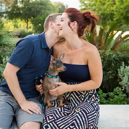 dog kissing man - A couple playing with their small dog in the park. Stock Photo - Premium Royalty-Free, Code: 6118-07781671