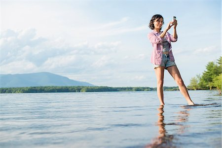 A woman standing in a lake in summer. Taking a photograph. Stock Photo - Premium Royalty-Free, Code: 6118-07781763