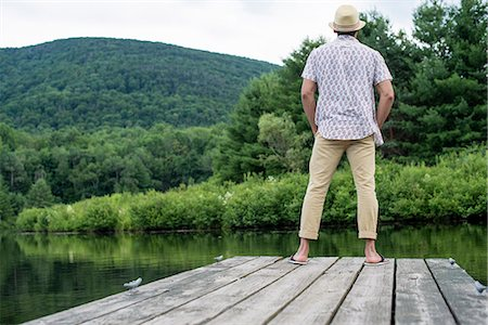 A man standing on a wooden pier overlooking a calm lake. Stock Photo - Premium Royalty-Free, Code: 6118-07781735
