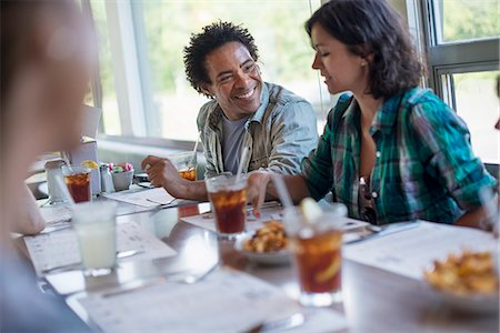 A group of friends eating at a diner. A couple seated side by side. Stock Photo - Premium Royalty-Free, Code: 6118-07781804