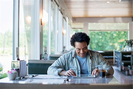 restaurant - A man sitting in a diner using a digital tablet. Stock Photo - Premium Royalty-Free, Code: 6118-07781811