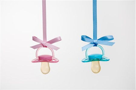 pink - Baby pacifiers hanging from ribbons against a plain background. Stock Photo - Premium Royalty-Free, Code: 6118-07731775