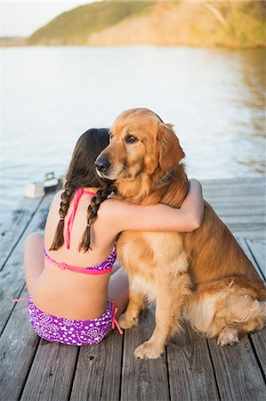preteen bathing suit - A young girl and a golden retriever dog sitting on a jetty. Stock Photo - Premium Royalty-Free, Code: 6118-07731782