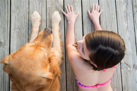 preteen bathing suit - A young girl and a golden retriever dog side by side on a jetty. Stock Photo - Premium Royalty-Free, Code: 6118-07731786