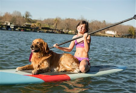 A child and a retriever dog on a paddleboard on the water. Stock Photo - Premium Royalty-Free, Code: 6118-07731793