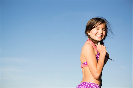 A young child in a bikini with plaited hair. Stock Photo - Premium Royalty-Free, Code: 6118-07731797