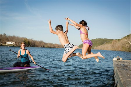 Two children leaping into the water from a jetty. Stock Photo - Premium Royalty-Free, Code: 6118-07731795