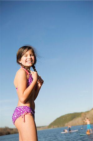 A young girl on a jetty with paddleboarders in the background. Stock Photo - Premium Royalty-Free, Code: 6118-07731798