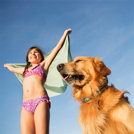 A girl in a beach towel with a golden retriever dog. Stock Photo - Premium Royalty-Free, Code: 6118-07731802