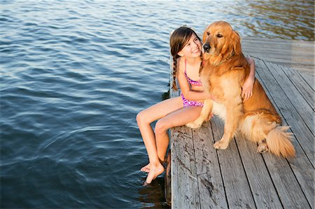 preteen bathing suit - A girl and her golden retriever dog seated on a jetty by a lake. Stock Photo - Premium Royalty-Free, Code: 6118-07731807