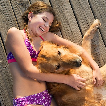 preteen bathing suit - A girl in a bikini lying beside a golden retriever dog, viewed from above. Stock Photo - Premium Royalty-Free, Code: 6118-07731805