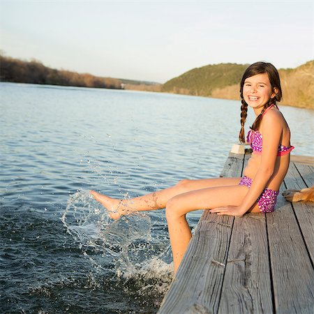 preteen girl swimsuit - A girl in a bikini sitting on a jetty with her feet in the water. Stock Photo - Premium Royalty-Free, Code: 6118-07731806