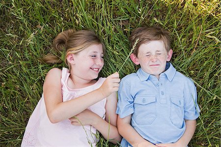 elementary age - Two children, brother and sister lying side by side on the grass Stock Photo - Premium Royalty-Free, Code: 6118-07731955