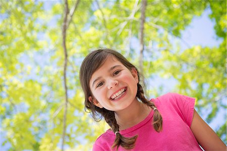preteen open mouth - A young girl with braids wearing a pink top under a canopy of trees. Stock Photo - Premium Royalty-Free, Code: 6118-07731979