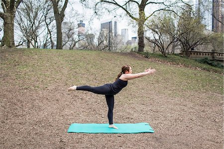 A young woman in Central Park, in a black leotard and leggings, doing yoga. Stock Photo - Premium Royalty-Free, Code: 6118-07731913