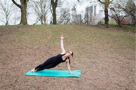 A young woman in Central Park, in a black leotard and leggings, doing yoga. Stock Photo - Premium Royalty-Free, Code: 6118-07731916