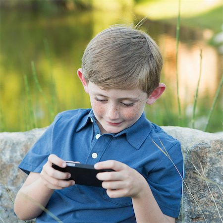A young boy outdoors sitting leaning against a rock, using a handheld electronic game. Stock Photo - Premium Royalty-Free, Code: 6118-07732035