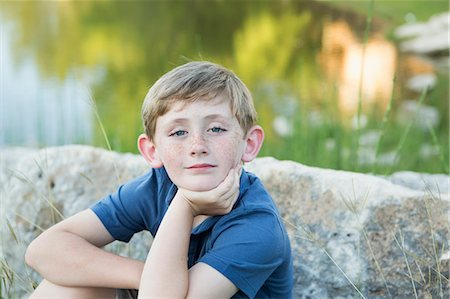 Head and shoulders portrait of a young boy sitting with his chin resting on his hand. Stock Photo - Premium Royalty-Free, Code: 6118-07732039