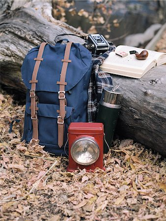 Hiking equipment, a backpack, torch, flask and camera by a tree trunk. A pipe lying on an open book. Stock Photo - Premium Royalty-Free, Code: 6118-07944767