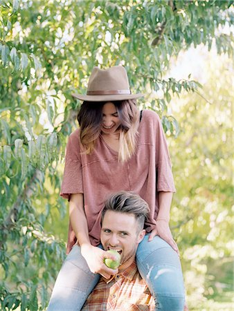 An apple orchard in Utah. man carrying a woman on his shoulders, eating an apple. Stock Photo - Premium Royalty-Free, Code: 6118-07944784