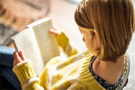 High angle view of a blond girl in a yellow jumper sitting on a chair, reading a book. Stock Photo - Premium Royalty-Free, Code: 6118-07966896