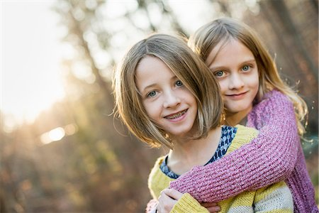Two smiling girls in a forest, hugging each other. Stock Photo - Premium Royalty-Free, Code: 6118-07966901