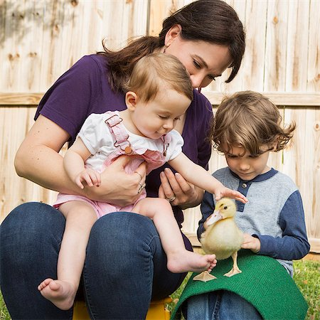 A woman and two children, with a young duckling. Stock Photo - Premium Royalty-Free, Code: 6118-08081848