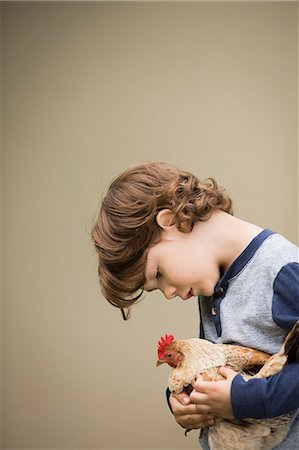 A small boy holding a chicken in his arms. Stock Photo - Premium Royalty-Free, Code: 6118-08081860