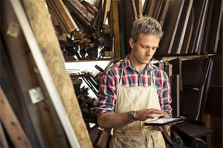 An antique furniture restorer in his workshop, using a digital tablet. Stock Photo - Premium Royalty-Free, Code: 6118-08088596