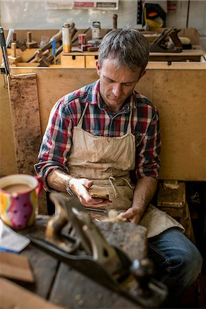 An antique furniture restorer in his workshop, using a smart phone. Stock Photo - Premium Royalty-Free, Code: 6118-08088603