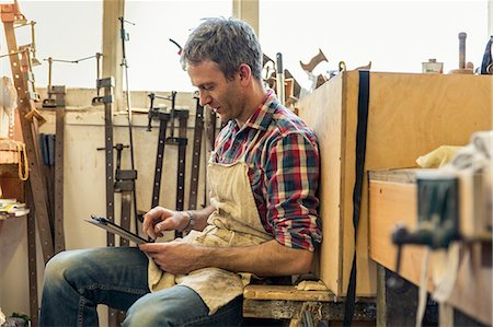 An antique furniture restorer seated in his workshop uisng a digital tablet. Stock Photo - Premium Royalty-Free, Code: 6118-08088600