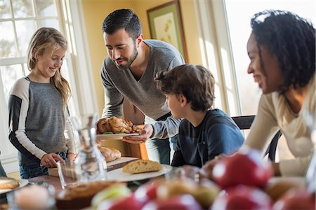 Adults and children gathered around a table for a meal. Stock Photo - Premium Royalty-Free, Code: 6118-08001557