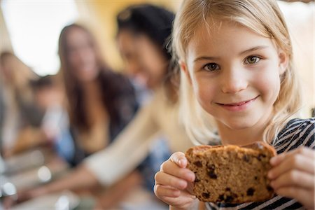 domestic life - A young girl with a large cookie. Stock Photo - Premium Royalty-Free, Code: 6118-08001555