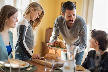 Adults and children gathered around a table for a meal. Stock Photo - Premium Royalty-Free, Code: 6118-08001556