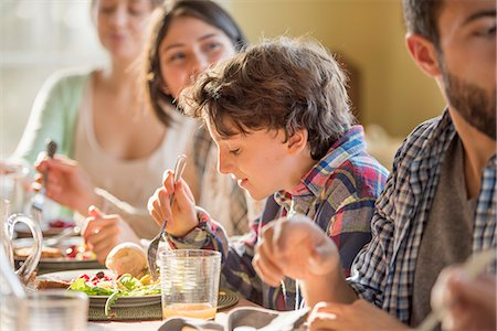 A group of people, adults and children, seated around a table for a meal. Stock Photo - Premium Royalty-Free, Code: 6118-08001577