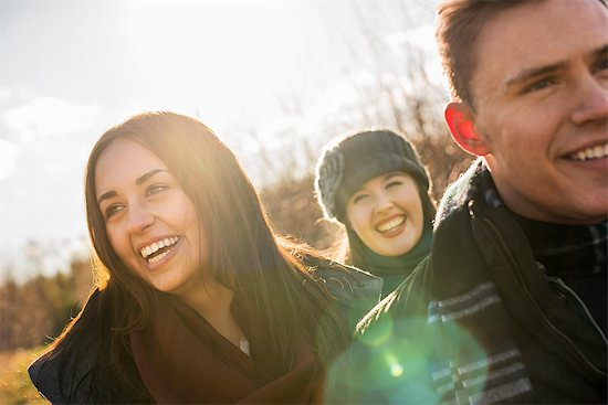 Three people, two women and a man in warm coats on a walk. Stock Photo - Premium Royalty-Free, Image code: 6118-08001594