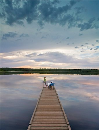 A couple, man and woman sitting at the end of a long wooden dock reaching out into a calm lake, at sunset. Stock Photo - Premium Royalty-Free, Code: 6118-08001595